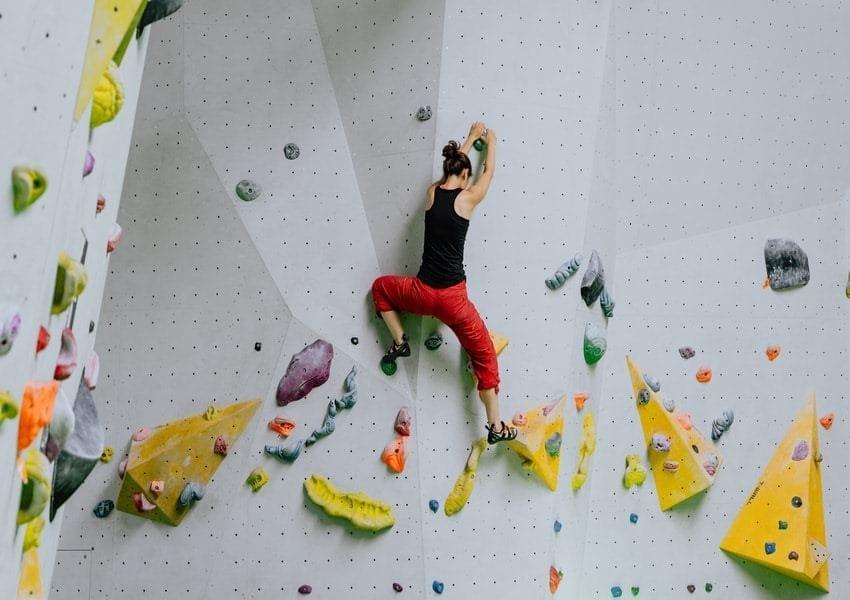 Una ragazza si arrampica su una parete artificiale in palestra
