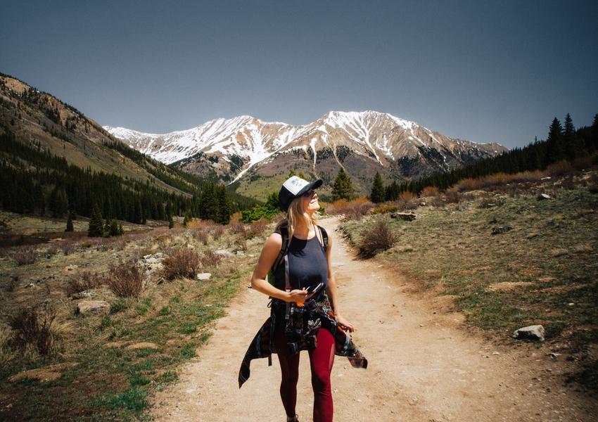 Una ragazza con canottiera e camicia annodata in vita cammina in montagna