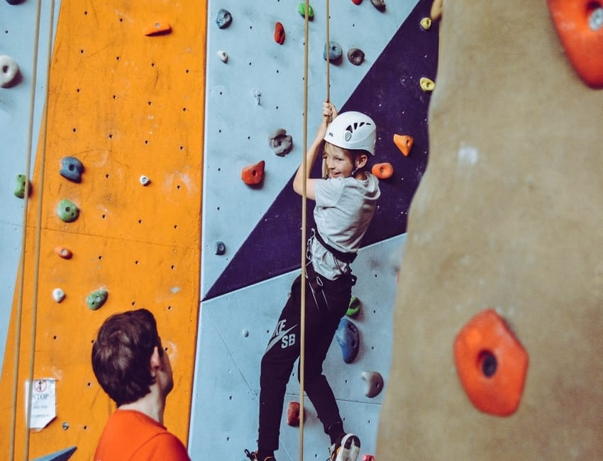 A girl is learning to climb on an indoor climbing wall