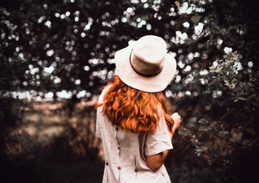 Una ragazza indossa un cappello a larga tesa in paglia
