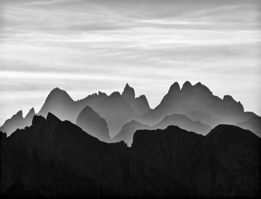A black and white picture of the peaks of the Dolomites