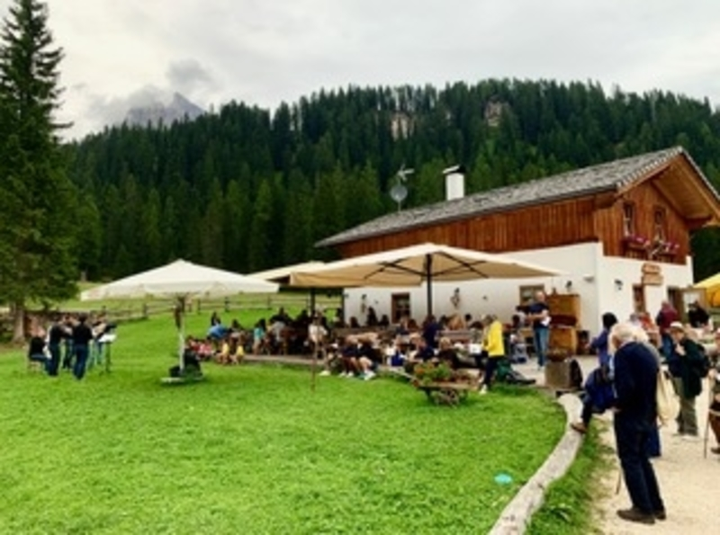 People listen to a concert on the grass around a small Rifugio in the Dolomites